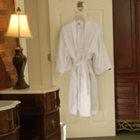 Table lamp and white robe hanging on a door at the Inn at St. John.