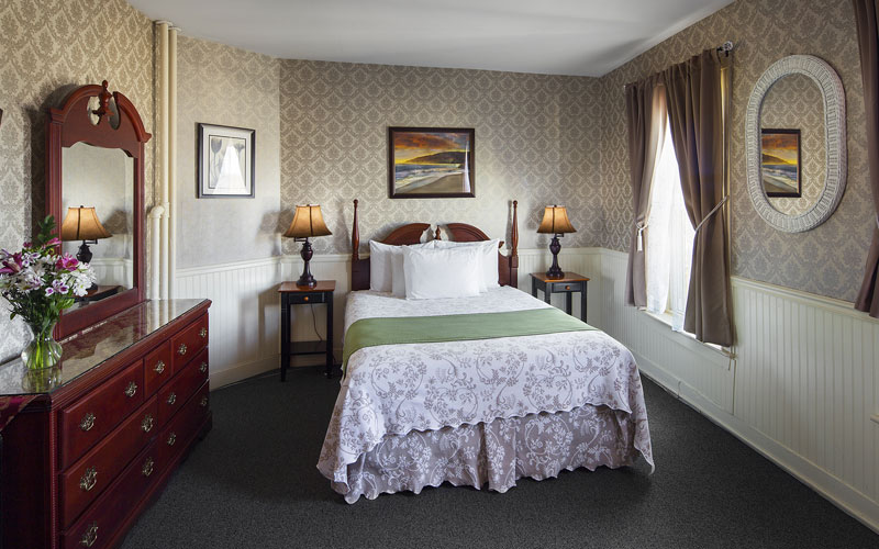 Queen bed in a traditional accommodation room at the Inn at St. John in Portland, Maine.