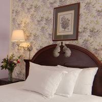 Queen size bed with white pillows and wood headboard of the Portland hotel Inn at St. John.
